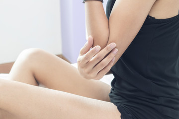 woman posing perfect healthy body shape and massaging her elbow
