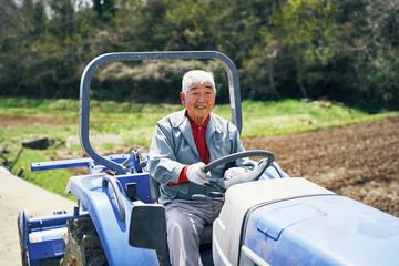 Senior man driving tractor