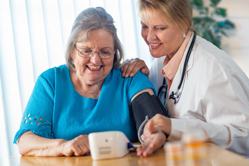 Senior Adult Woman Learning From Female Doctor to Use Blood Pressure Machine