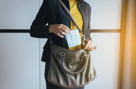 Woman hand putting sanitary napkins in handbag,White menstrual pad