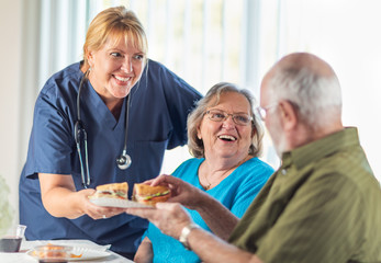 Female Doctor or Nurse Serving Senior Adult Couple Sandwiches at Table