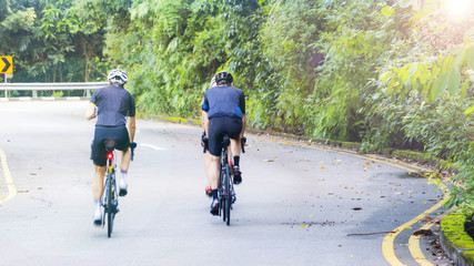 Back view of sporty people cycling on road in the park