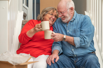Tired Senior Adult Couple Resting on Stairs with Cups of Coffee Surrounded with Moving Boxes