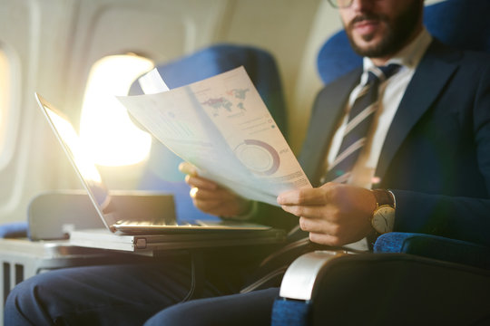 Crop portrait of modern bearded businessman reading documents and working while enjoying flight in first class, copy space