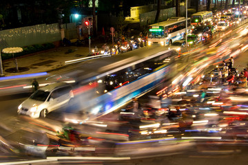 Dense traffic at night intersection with blurred lights passing through motorbikes and vehicles.
