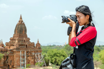 The tourist in Burma is photographing historical monuments. Young woman with camera in Myanmar.