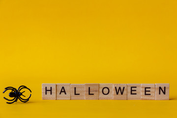 Halloween wooden blocks with spiders on yellow background, Halloween background