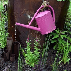 Fountain made out of a pink watering can in garden