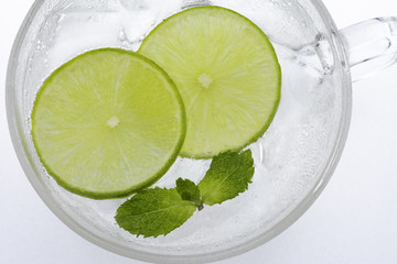 Glass of lemonade with  green lemon slices and mint.