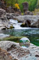 Crystal glass ball sphere sitting on rock with waterfall in background
