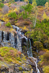 A waterfall on a hillside covered in colorful autumn trees and shrubs, British Columbia, Canada
