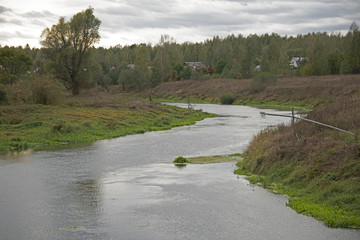 Russian rural landscape - small village on the river bank