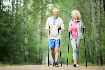 Senior active couple practicing trekking in park among green trees on summer weekend