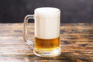 Glass of beer on wooden table. A mug of beer