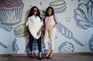 Two stylish african american girls at cafe posed against wall.