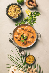 Traditional curry and ingredients on concrete background