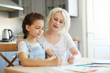 Young blonde female looking at her daughter drawing while both sitting in the kitchen