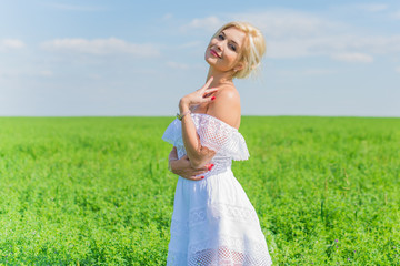 Freedom concept. Young happy woman in green field, evening light. Blue sky behind. Beauty Girl Outdoors enjoying nature. Beautiful Model girl in white dress running on the meadow