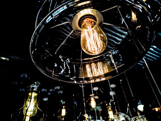 Tungsten orange light bulb hanging on the inside of the building with a black iron fence around,Lighting in buildings with multi-colored electric lamps,soft focus.