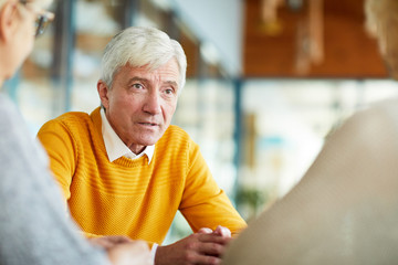 Serious confident senior man with gray hair wearing yellow sweater talking to colleagues while they discussing business in cafe
