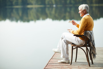 Happy relaxed handsome senior man wearing stylish clothing sitting on old chair with blanket on pier and drinking coffee while contemplating lake