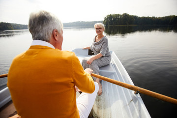Happy attractive elderly lady in dress and glasses sitting on boat and looking at man while they riding boat during beautiful date on lake