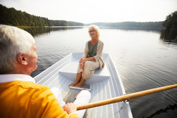 Smiling senior lady in glasses looking with love and tenderness at boyfriend who rowing boat and enjoying date on boat