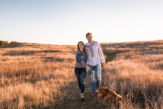 Happy young couple is walking with dog.