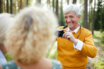 Jolly excited handsome senior man in yellow sweater photographing friends on camera and laughing while asking them to pose in forest