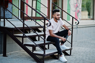 Stylish indian beard man at pink t-shirt. India model sitting on stairs outdoor at streets of city.