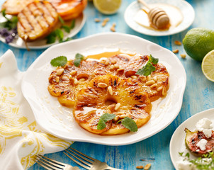 Pineapple dessert, Grilled slices of pineapple with the addition honey, roasted pine nuts,  fresh lemon balm and cinnamon. Delicious and healthy vegetarian food, fruity dessert