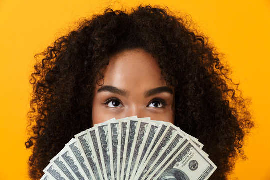 Woman posing isolated over yellow background holding money covering face.