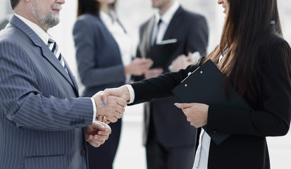 assistant meets a businessman with a handshake. meetings and partnership