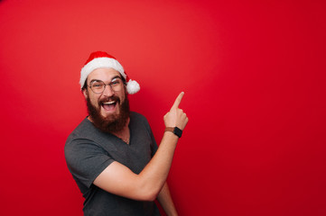 Amazed bearded man wearing santa claus hat pointing away over red background