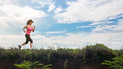 Athletic woman running up the mountain work-out outdoor.