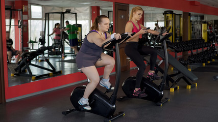 Plump woman working hard at stationary bike to achieve results, fitness, sport