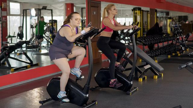Overweight lady riding sluggishly exercise bike and scrolling smartphone, lazy