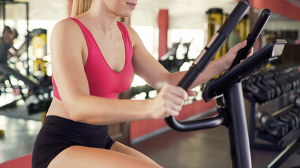 Slim woman riding exercise bike at sports club, healthy lifestyle, sports