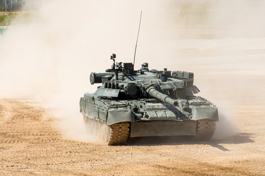 Powerful military tank rides at a high speed along the dusty field.