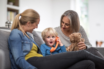 Child playing with a toy phone with mother and grandmother
