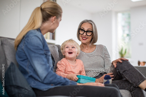 Boy opening a birthday present with grandmother and mother