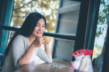 Beautiful attractive young Asian woman holding a cup of coffee in hand and sitting on sofa at cafe in the morning, vintage color tone.