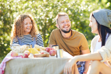 Three young people laughing while discussing something funny by served table in natural environment