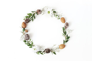 Christmas circle floral composition. Wreath of eucalyptus branches, larch cones, almonds, chrysanthemum and baby's breath flowers on white background. Winter wedding design. Flat lay, top view.