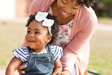 African American mother laughing and holding her daughter.