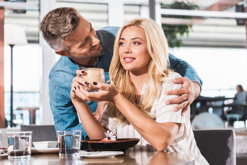 handsome boyfriend hugging girlfriend near table in cafe, she holding glass of coffee