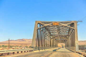 Iron bridge over the railroad in Barstow California on the historic Route 66 with Mojave desert on background. North 1st Street Bridge.
