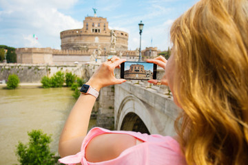Woman taking photo of famous Castel Sant'Angelo in Rome, Italy