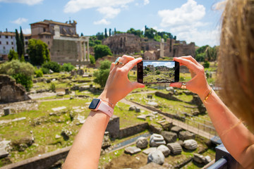 Tourist taking photo with mobile phone in ancient Rome
