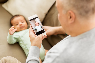 family, fatherhood and people concept - close up of father photographing little baby son by smartphone at home
